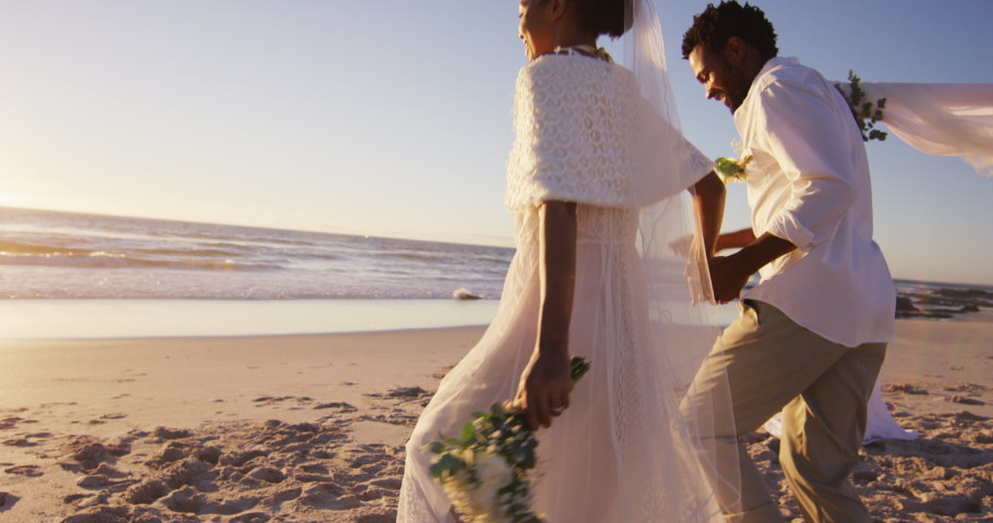 African american couple in love getting married, holding hands on the beach at sunset. marriage, love and romance, holiday by the sea.