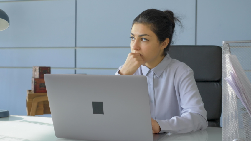 A Young Indian Woman Freelancer Works On An Online Project At A Computer Laptop, A Programmer Writes Code And Does Management In A Home Office In A Bright Room Royalty-Free Stock Footage #1069792636