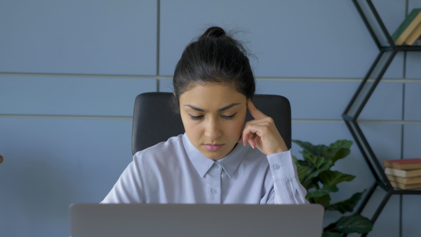 Close-Up Portrait Of A Young Indian Woman Looking Thoughtfully At A Monitor Screen, A Freelancer Working On An Online Project At A Laptop Computer, A Programmer Writing Code And Doing Management In A  Royalty-Free Stock Footage #1069792663