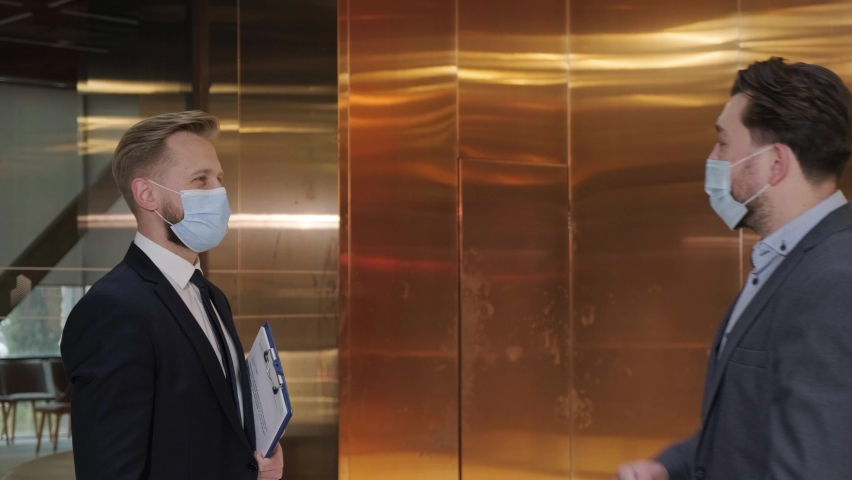Two businessmen avoid a handshake when meeting in the business building and greet with elbows bumping, wearing a medical mask to protect himself. Royalty-Free Stock Footage #1069799422