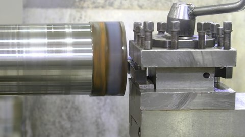 The operation of lathe machine cutting the metal shaft parts. The metalworking process by turning machine.