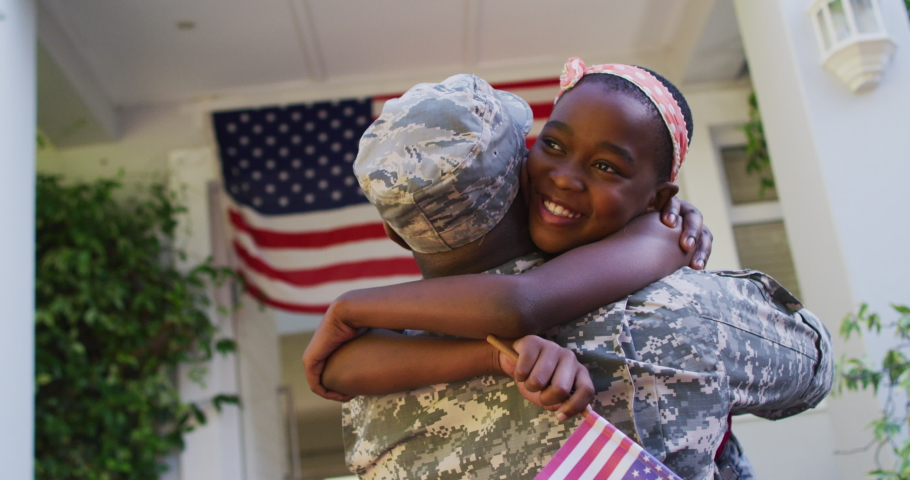 African american soldier father hugging smiling daughter in front of house with american flag. soldier returning home to family.