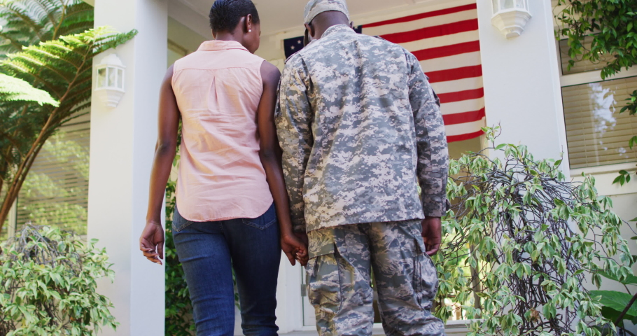 Happy african american male soldier and wife holding hands walking to house with american flag. soldier returning home to family.