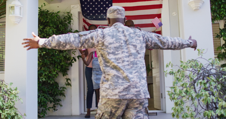 African american soldier father hugging his excited family front of house with american flag. soldier returning home to family.