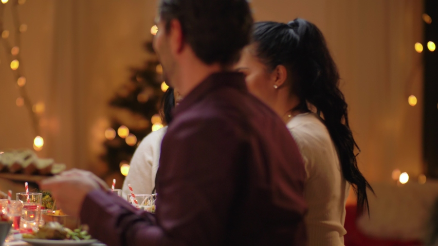 Winter holidays, celebration and people concept - happy friends having christmas dinner at home   Shutterstock HD Video #1069851367