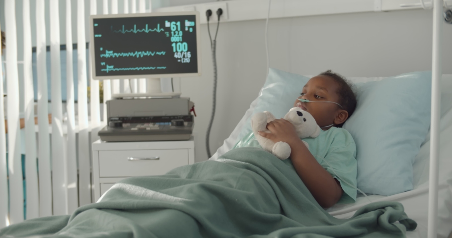 Afro-american kid lying in hospital bed with oxygen tube and plush toy. Portrait of sick and sad african child patient resting in bed at hospital ward with modern equipment Royalty-Free Stock Footage #1069896286