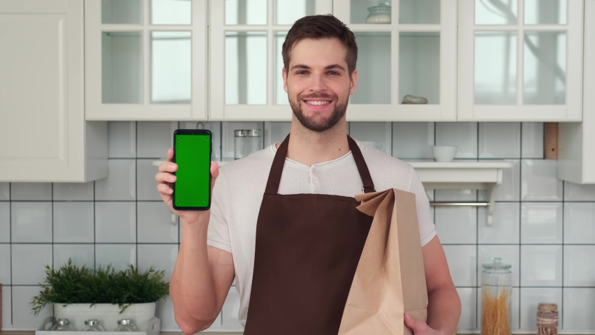 Vegan Cooking, Male Chef, Healthy Eating, Food Delivery. A man in an apron holds a smartphone with a green screen in his hand and smiles. Home delivery app Royalty-Free Stock Footage #1069908544