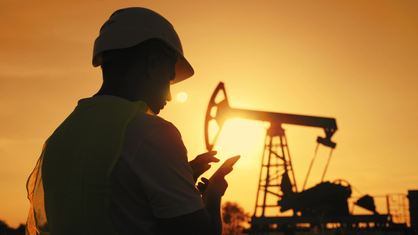 Silhouette working engineer oil rig. Oil rigs at sunset. Silhouette of man engineer with phone overseeing the site of crude oil production at sunset. Industrial, oil and gas concept.