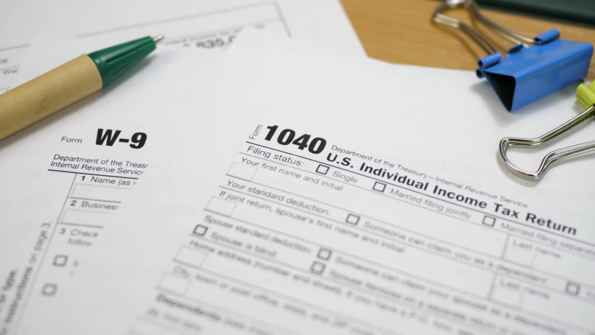 Blank W-9 and Form 1040 U.S. individual income tax return with pen. Tax payment concept. Filing taxes document Royalty-Free Stock Footage #1069940173