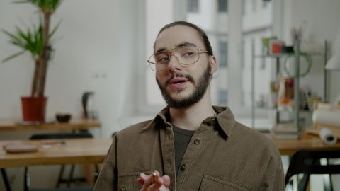 Professional company manager talks to workers explaining startup and holding pencil at online meeting in office slow motion