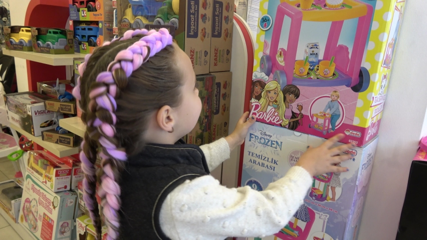Fethiye, Turkey - 25th of March 2021: 4K Young girl with two braids examines boxes of brand toys