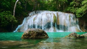 Fairy waterfall at wild forest. Wonderful fresh water waterfalls river flowing. Forest rocks with a roaring stream running. Panoramic sun landscape of nature waterfall. Fresh nature. Loop video. 4K