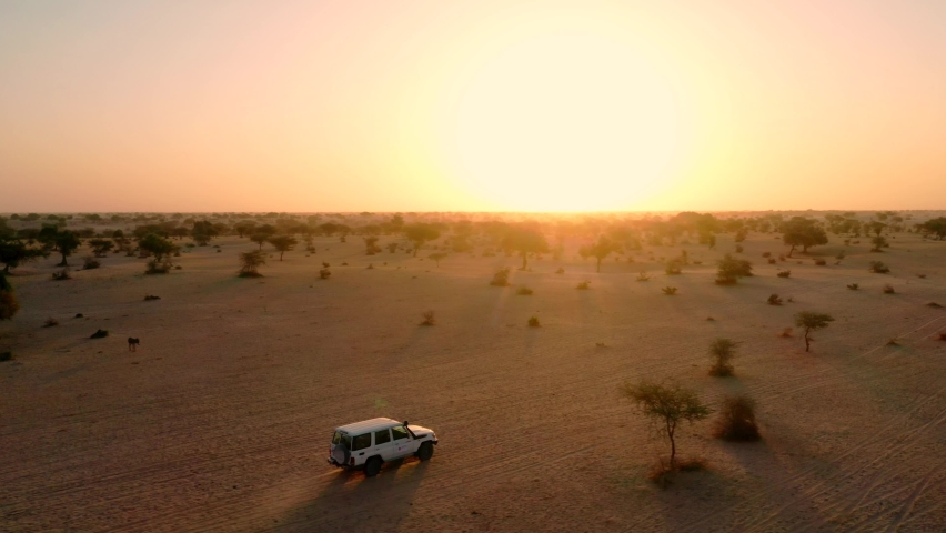 Drone tracking of a car driving in the Sahara desert of Chad, Africa, at sunrise | Shutterstock HD Video #1069968748