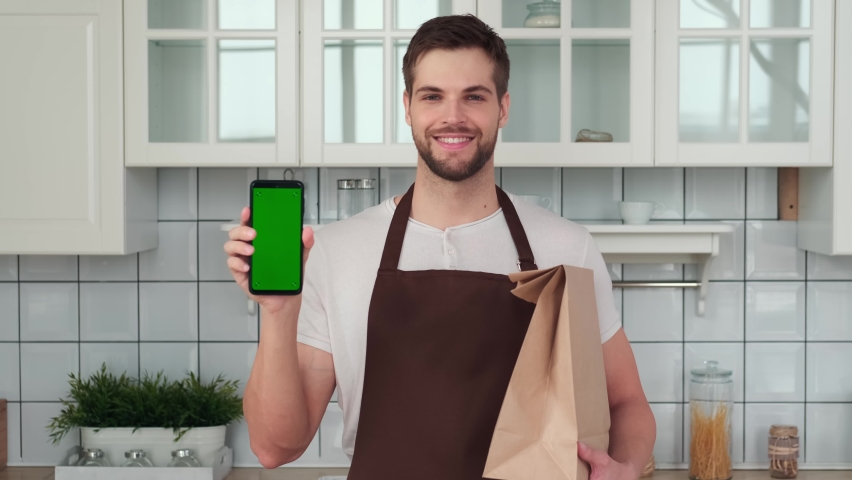 Vegan Cooking, Male Chef, Healthy Eating, Food Delivery. A man holds a smartphone with a green screen in his hand and smiles while standing in the kitchen. Home delivery app Royalty-Free Stock Footage #1069970149
