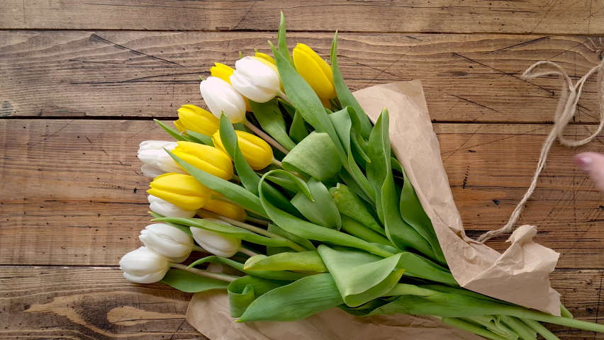 Hands untie a tulips bouquet and touch a flower on a wooden table top view  Royalty-Free Stock Footage #1069973281