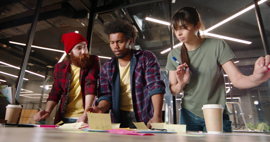 Millennial students discussing ideas for project and arguing. Creative diverse team brainstorming in office, making plans and strategies - teamwork, education low angle 4k footage Royalty-Free Stock Footage #1069994965