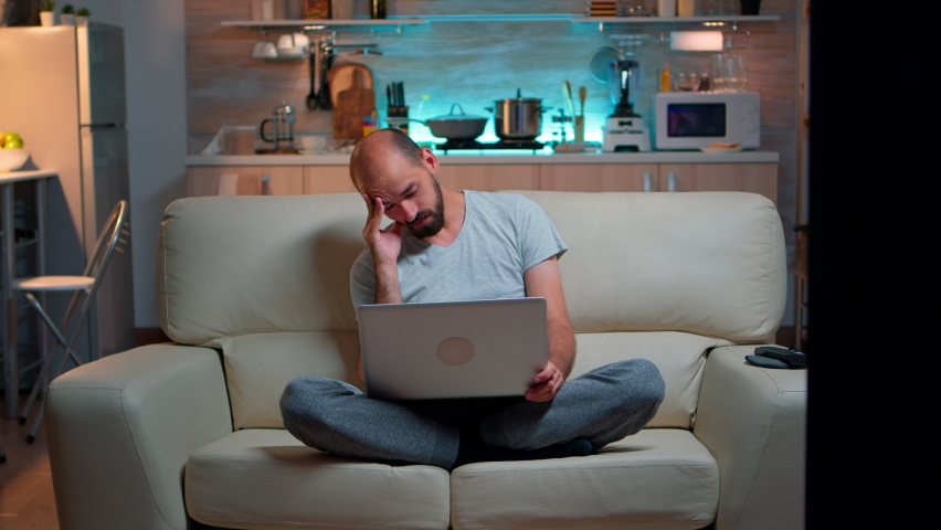 Business communication project video call meeting on zoom call. Remote focused man on sofa using conference call internet chat work from home web conversation and online video conference lat at night
