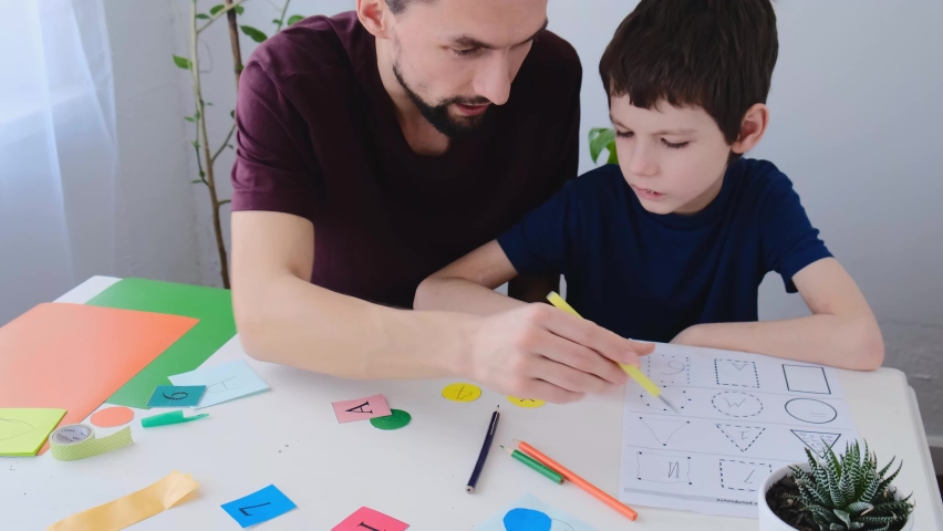 Autism boy during therapy with his school tutor, learning together. Autism childhood mental illness therapy concept Royalty-Free Stock Footage #1070019082