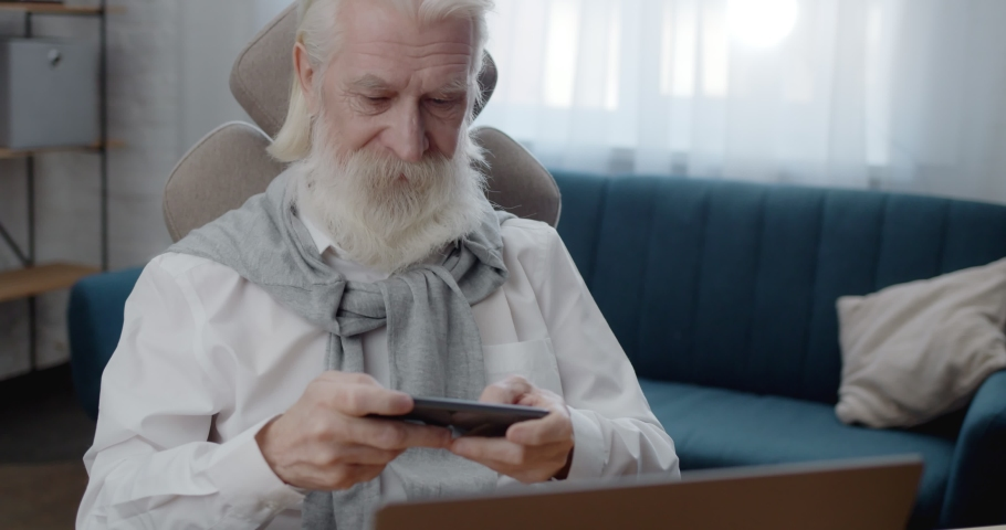 Attractive Old Male playing game on Phone using Apps while sitting at Home. Confident Retired Man enthusiastic about new Device. Resting at house. Enjoys modern technology. Quarantine. Safe Distance. | Shutterstock HD Video #1070020144