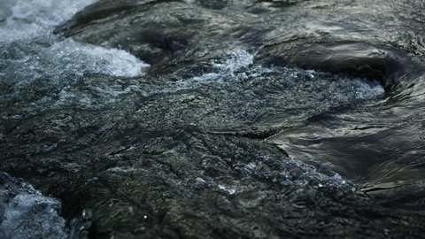 Closeup of mountain river surface. Abundant water stream flowing through stone rapids in slow motion. Surface of wild flow swirling in mountain river. Bubbling clear water in cascade of boulders.