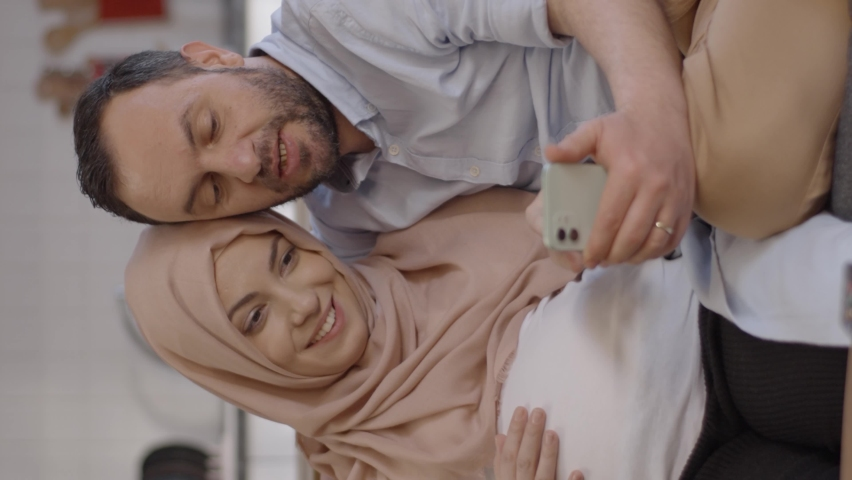 Online baby shopping concept.Muslim wife in pregnant turban and her husband shop for babies on their mobile phones.Video for the vertical story. Royalty-Free Stock Footage #1070042662