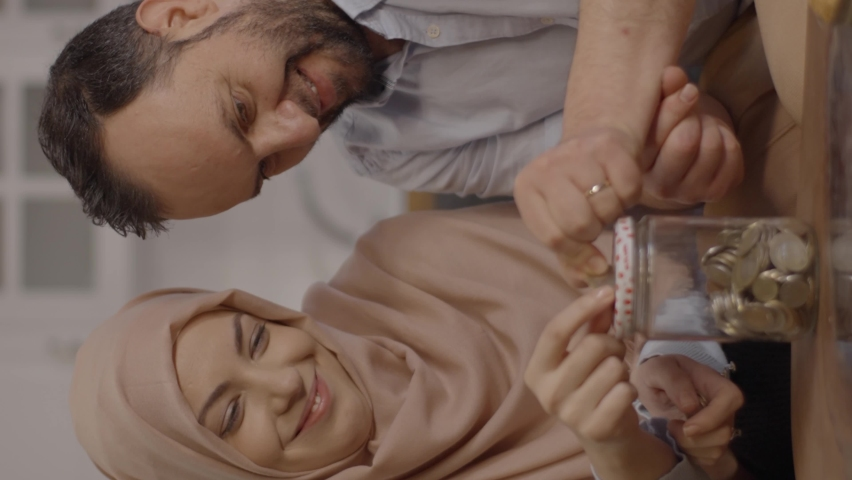 The Muslim woman wearing a headscarf and her husband throwing money into the jar money box one by one save money.Save up money concept.Video for the vertical story. Royalty-Free Stock Footage #1070042713