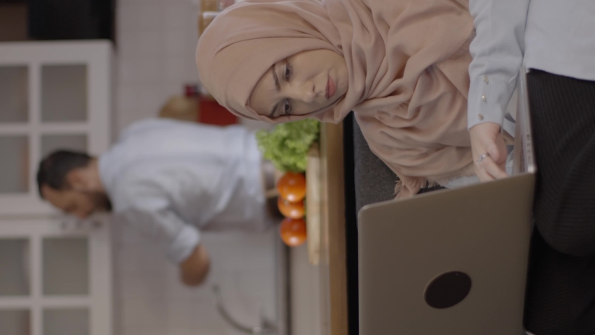 A young woman in hijab, working from home, describes what she should do to her husband, who prepares a meal in the kitchen. Remote working concept.Video for the vertical story. Royalty-Free Stock Footage #1070042752