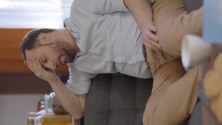 A bearded young man at home with aching shoulders and headaches.The man is rubbing his head, face and neck.Video for the vertical story. Royalty-Free Stock Footage #1070042788