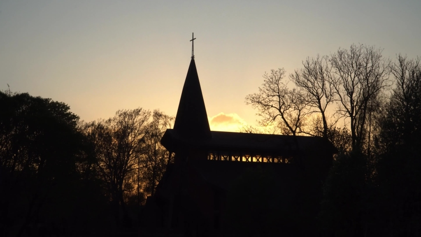 The church building landscape in spring with sunset lights background. Between the black silhouettes of trees visible the spire of the tower. The architecture of modern religious constructions. Royalty-Free Stock Footage #1070117089