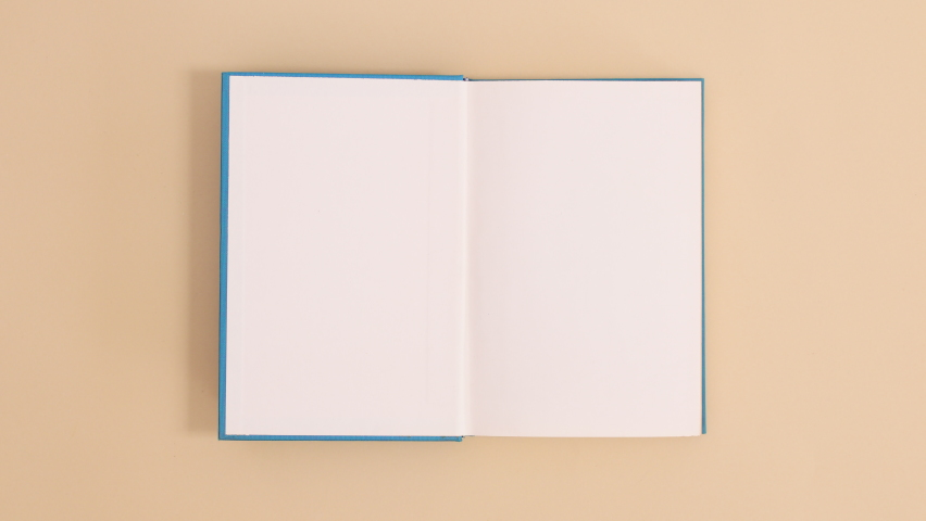 6k Blue hardcover vintage book appear and open with copy space on beige background. Stop motion flat lay Royalty-Free Stock Footage #1070120566