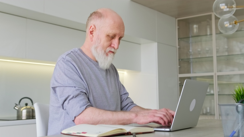 Cute 70-year-old gray-haired old man with beard at age of using computer browsing Internet, reading an e-book in application communicates online via video link with doctor. Distance learning old man. Royalty-Free Stock Footage #1070140732