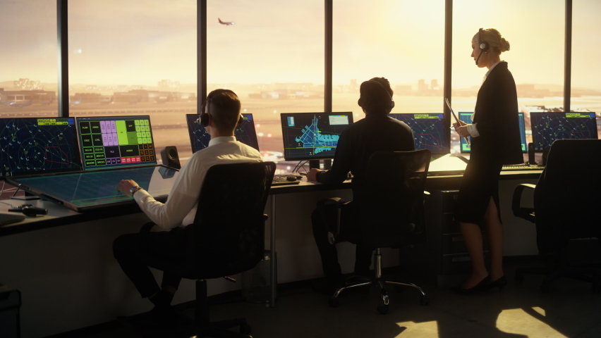 Diverse Air Traffic Control Team Working in a Modern Airport Tower at Sunset. Office Room is Full of Desktop Computer Displays with Navigation Screens, Airplane Flight Radar Data for Controllers.