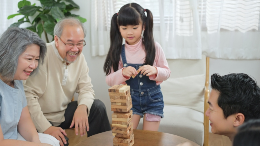 Asian family stay at home, enjoying activity relationship in living room. Senior grandparents, father and mother playing Jenga or Tumbling tower wood block game with little cute kid daughter in house.