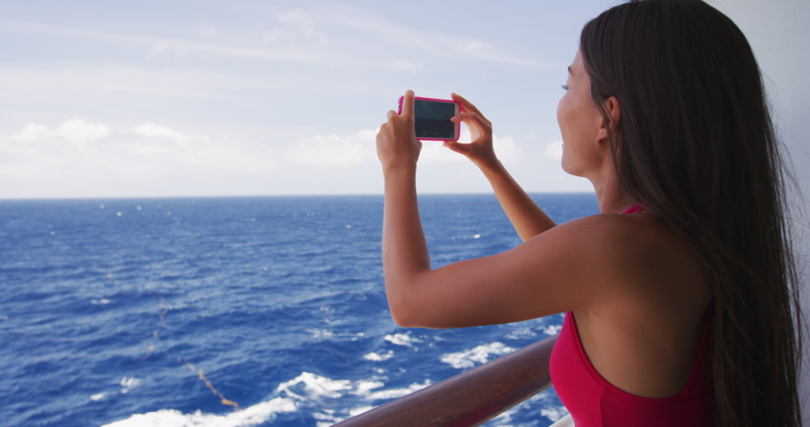 Cruise ship vacation woman taking photo with phone camera enjoying travel at sea. Girl using smartphone app to take picture of ocean. Woman in dress on luxury cruise liner boat.