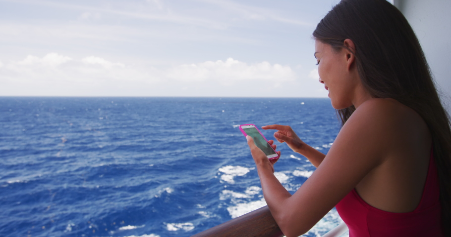 Cruise ship woman using phone on travel vacation at ocean. Asian girl using social media looking at picture on wifi on tropical holidays. Internet on international seas concept. Tourist.