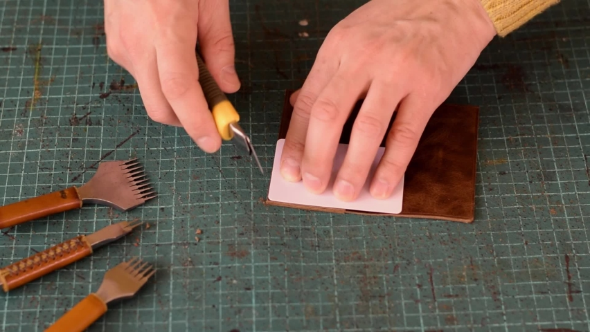 Artisan uses a knife to round the corners of the leather cardholder. Production of handmade leather goods.Hobby concept. Slow-motion, close-up. Royalty-Free Stock Footage #1070215933