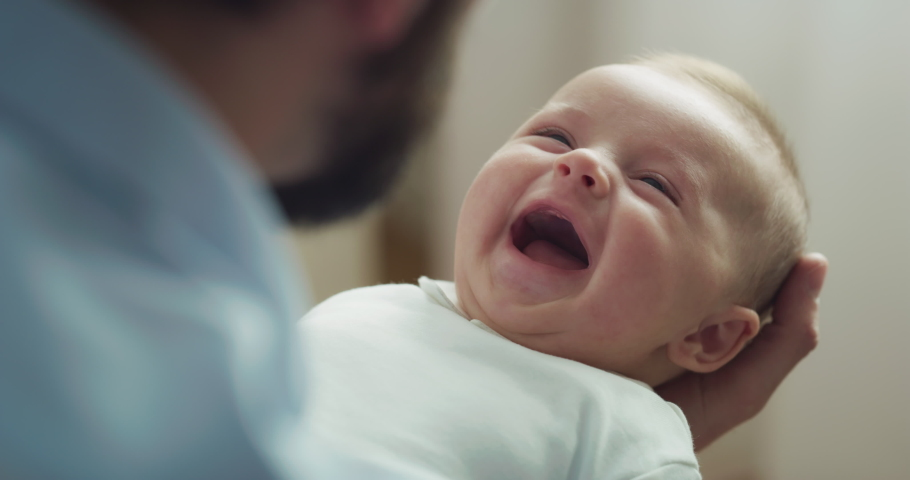 Cinematic close up shot of young neo father is playing with his newborn baby in a nursery in a morning. Concept of children, baby, parenthood, childhood, life, love, fatherhood, family. Royalty-Free Stock Footage #1070237125