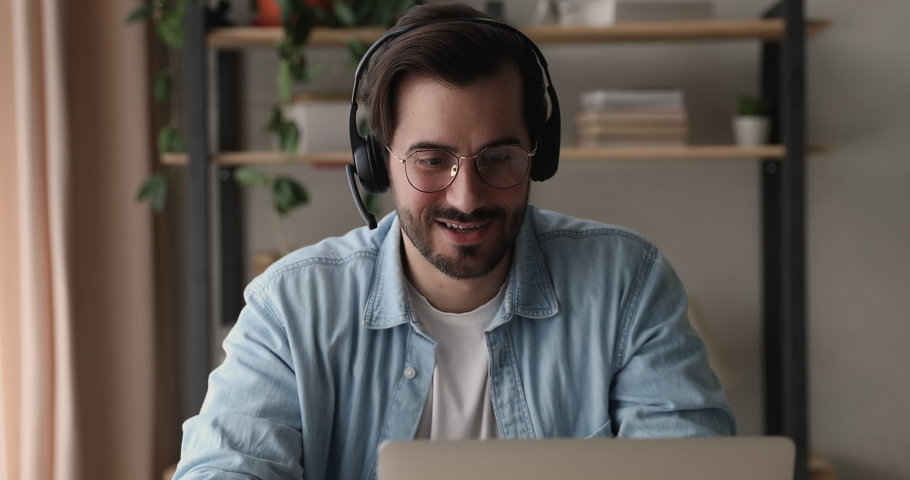 Millennial confident businessman sit at workplace look at laptop listen to client through headset talk to customer using remote web chat online video conference application. Video call event concept Royalty-Free Stock Footage #1070237950