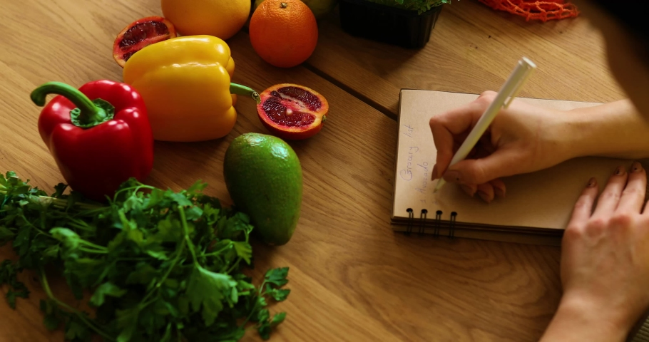 Woman planning, writing weekly meals on a meal planner note or diet plan on wooden table with healthy food fruit and vegetables in her kitchen at home. Royalty-Free Stock Footage #1070293096