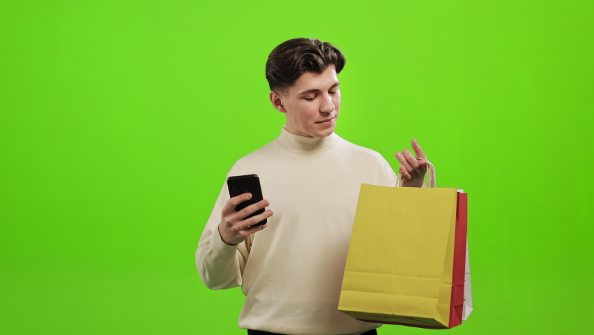A man is texting on a smartphone and holding shopping bags in his hands. He is raising his head and smiling. He is standing on a green background. Green screen. 4K Royalty-Free Stock Footage #1070296930