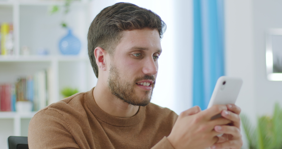 Young caucasian bearded millennial professional holding modern smartphone texting message at home. Young business man writing a text sitting at work desk. Royalty-Free Stock Footage #1070314435