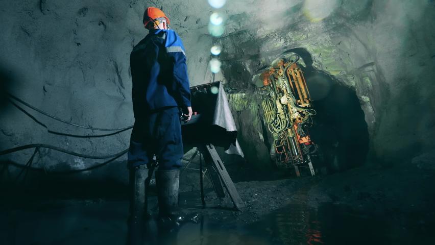 Underground development, underground extraction, underground mining operations. Boring machine is getting managed by a mine worker Royalty-Free Stock Footage #1070330905