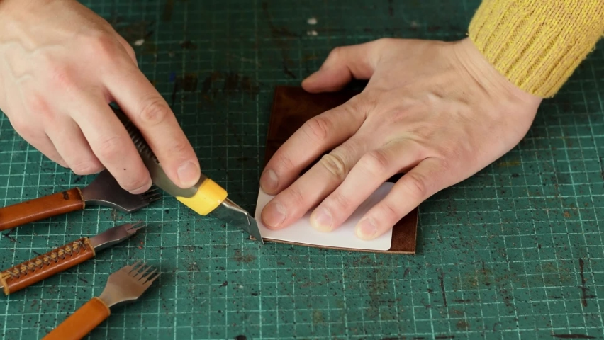 Artisan uses a knife to round the corners of the leather cardholder.Production of handmade leather goods.Hobby concept.Slow motion,close-up. Royalty-Free Stock Footage #1070349844
