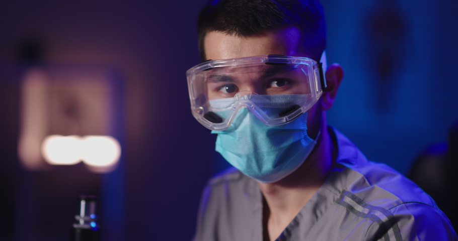 Close up shot of face of a doctor or scientist wearing facial mask and protection goggles looking at camera. Medicine worker at coronavirus times - pandemic 4k portrait footage