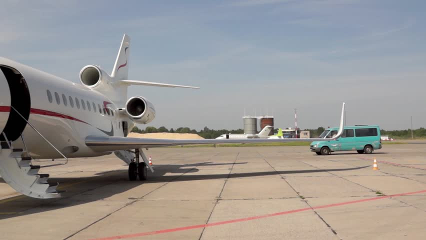Private Jet in Airport is waiting for passengers. Daytime. Another View
