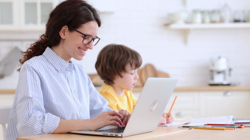 Family, lockdown distance job concept. Kid son painting while his mother is working on laptop at home office. Woman with her child doing homework or studying sitting together at table in living room.  Royalty-Free Stock Footage #1070390029