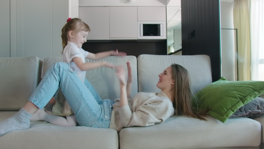 Happy Carefree Mother Babysitter And Cute Small Child Daughter Tickling Laughing Having Fun Lying On Sofa And Playing, Smiling Mum Enjoying Spending Time With Little Funny Kid At Home Royalty-Free Stock Footage #1070394448