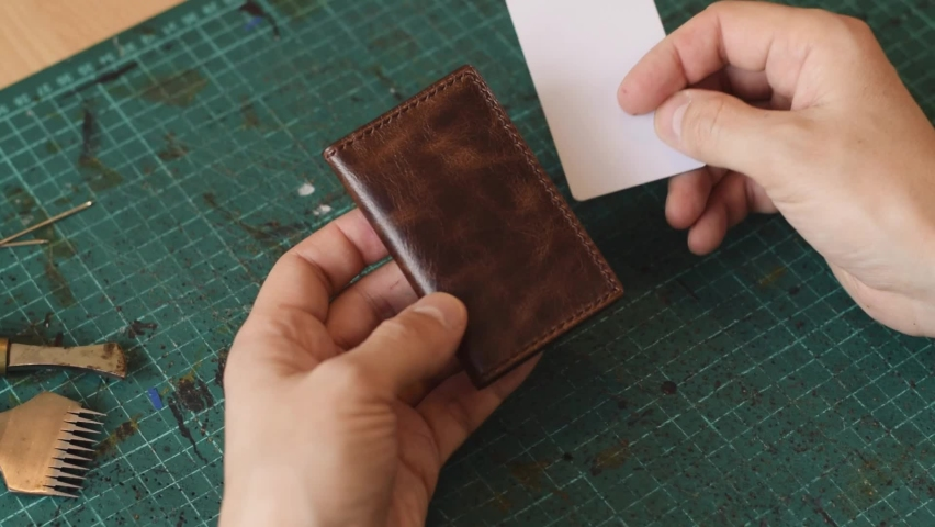 The process of manufacturing a goods made of genuine leather.Demonstration of the finished leather cardholder.Hobby concept. Slow-motion, close-up.  Royalty-Free Stock Footage #1070399353