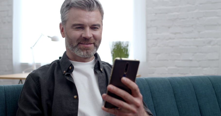 Handsome Businessman Browsing in Social Media on Mobile Phone, sitting at home. Attractive successful bearded Man, Leader scrolling posts, reading News using Smartphone Apps. Social Networks. Message. Royalty-Free Stock Footage #1070413723