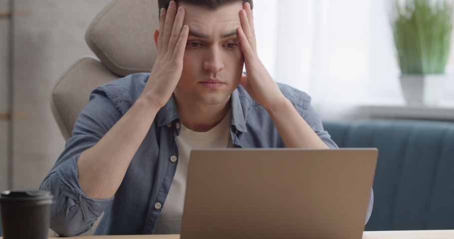 Shocked Businessman receives Message with Bad News from Business Partners. Stressed Student Looks at Laptop Screen feeling Frustrate, Reading Failed Exam Results sitting at Workplace. Problems.